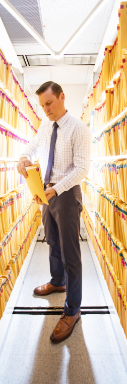 man in business attire looking at file