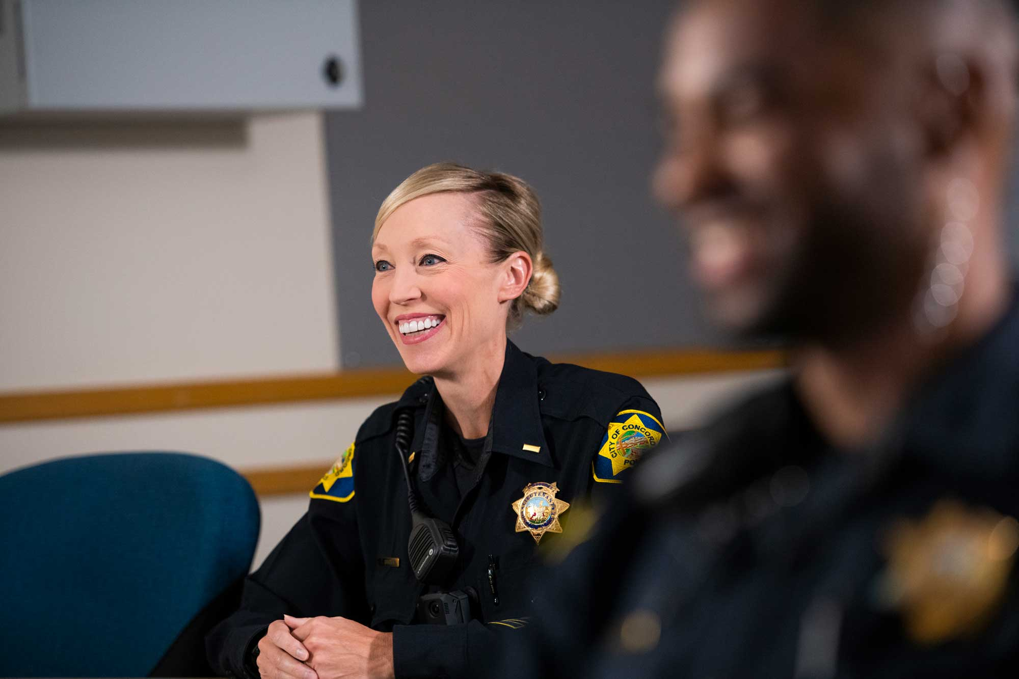 smiling female police officer in meeting
