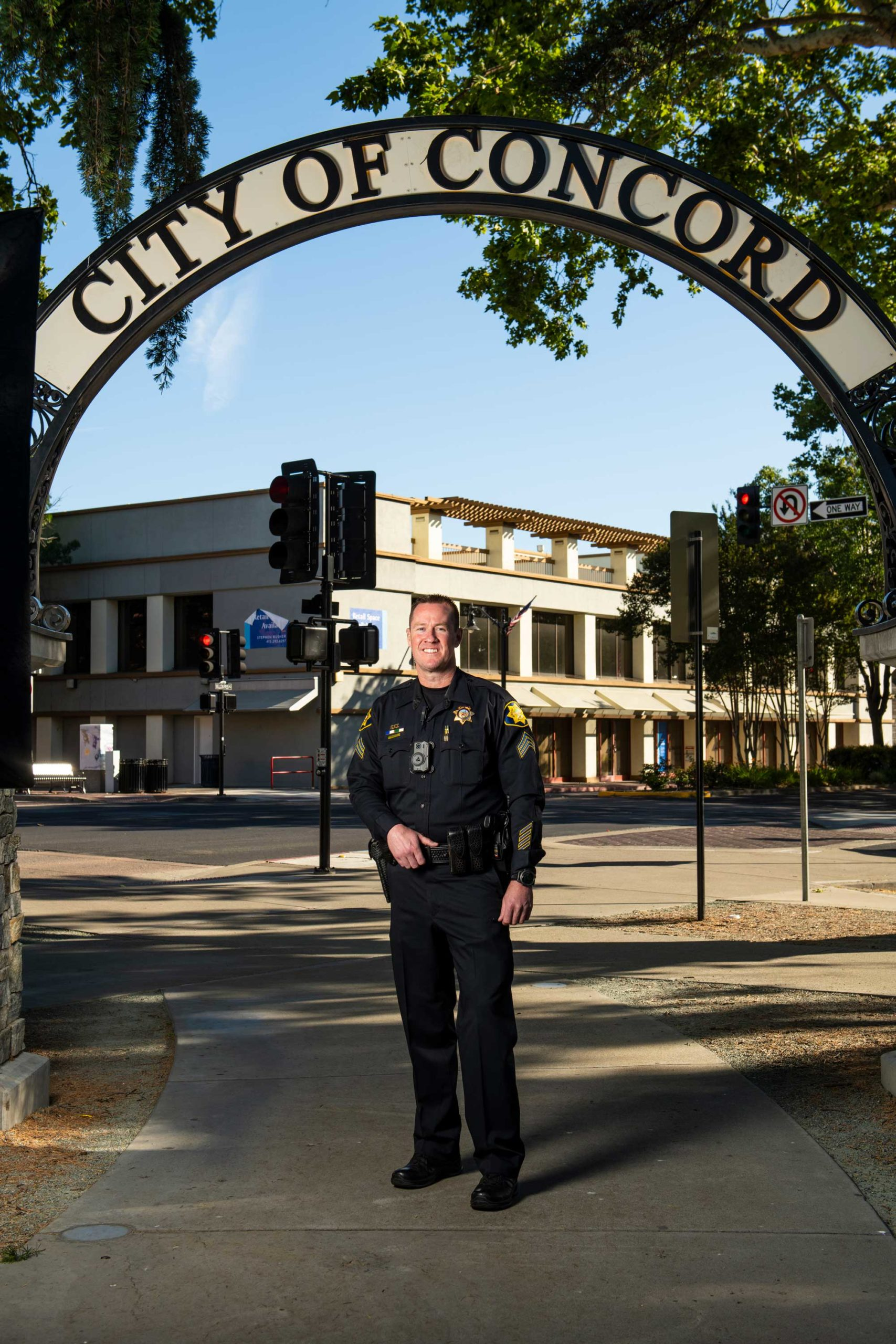 smiling police officer in uniform under City of Concord sign
