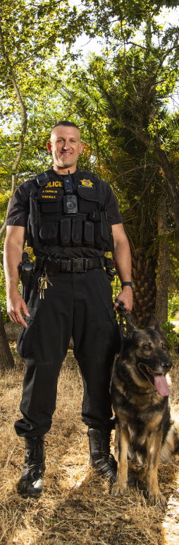 smiling uniformed police officer posing outdoors with K9 dog